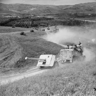 (IWM Caption) A 17pdr anti-tank gun and half-track of 269/87th Anti-Tank Regiment approaches the River Foglia, 1 September 1944.